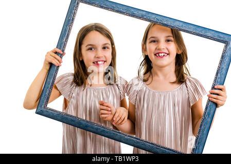Identische Zwillinge machen glücklich Ausdrücke mit Bilderrahmen. Kinder, Schwestern, Mädchen posiert im Studio mit Bilderrahmen, die verschiedenen f - Stockfoto
