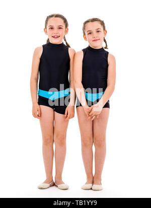 Portrait von Zwilling Mädchen in der Rhythmischen Gymnastik Kleid angezogen. Junge Zwillingsschwester Mädchen frontal Portrait im Tanzen sport Kleid. Auf w Isoliert - Stockfoto