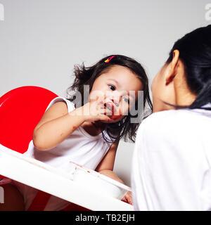 Asiatische Mutter Fütterung ein super cute adorable Baby Mädchen Schokolade in Ihrem Stuhl und sie bildet eine Verwirrung - Stockfoto
