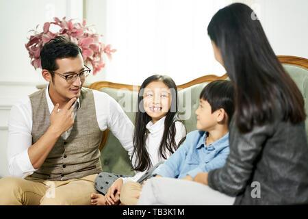 Junge asiatische Eltern und zwei Kindern auf der Couch Chatten in Familie Wohnzimmer zu Hause sitzen - Stockfoto