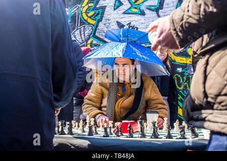 Shoreditch, London, England, UK - April 2019: Alter mann straße Schachspieler Schach spielen trug einen Regenschirm als Hut in der Brick Lane, East London - Stockfoto