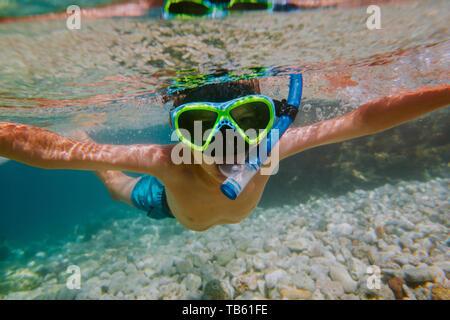 Kind Schnorcheln im flachen Meer. Junge mit Taucherbrille und Schnorchel schauen in die Kamera unter Wasser. - Stockfoto