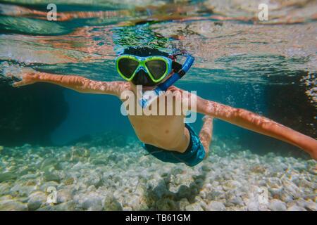 Kind Schnorcheln. Junge mit Taucherbrille und Schnorchel schwimmen im flachen Meer mit den Armen weit verbreitet. - Stockfoto