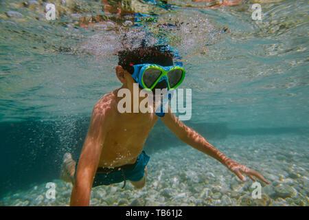 Kind Schnorcheln im flachen Meer. Junge mit Taucherbrille und Schnorchel, Tauchen zu lernen. - Stockfoto