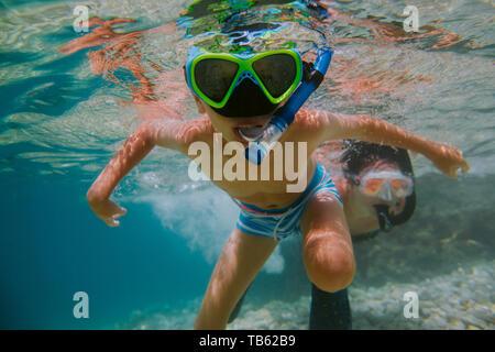 Kinder lernen mit seiner Mutter in Meer zu Schnorcheln. Junge tragen Taucherbrille Schwimmen unter Wasser. - Stockfoto