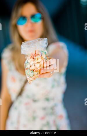 Eine Frau mit süßen Popcorn von kleinen Plastikbeutel - Stockfoto