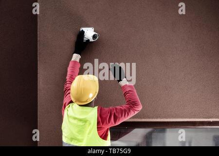 Professionelle CCTV-Techniker arbeiten. Techniker zur Festsetzung Kamera an der Wand - Stockfoto