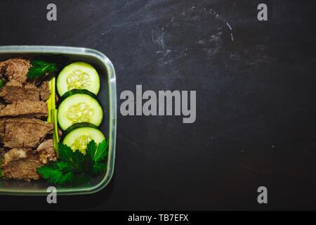 Gekochtes Rindfleisch und frische Gurke in einem kleinen Behälter auf einem schwarzen Hintergrund, Ansicht von oben, aus der Nähe. Gesunde Ernährung, Diät, Fitness. kopieren. - Stockfoto