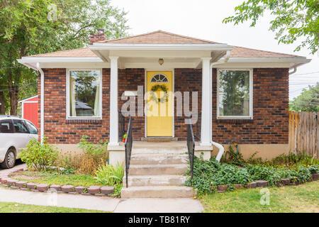 Fassade Blick auf kleine Ziegel Einfamilienhaus mit gelben Akzent Tür und große Fenster - Stockfoto