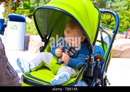 Kleiner Junge sitzt in Pram mit einem lächelnden Gesicht - Stockfoto
