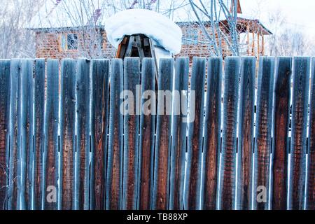 Ländliche Winterlandschaft mit Schneeverwehungen und schneebedeckten Bäumen und einem Holzzaun - Stockfoto