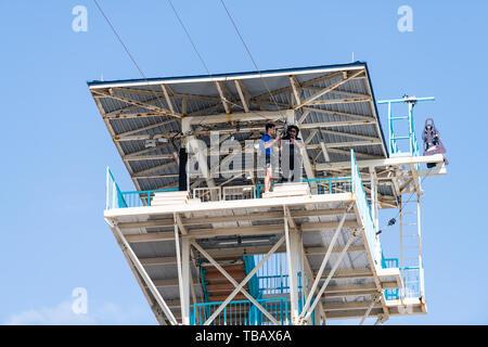Destin, USA - 24. April 2018: Die niedrigen Winkel, Blick auf die zipline Turm mit Arbeiter anbringen, Kabelbaum und afrikanische amerikanische Frau, Fertig - Stockfoto