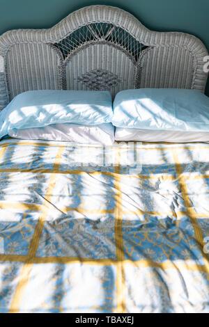 Nahaufnahme des Neuen sauberes Bett mit Daunendecke Wicker rattan Kopfteile vintage Beach Blue green Kissen in sonnige Schlafzimmer in Wohnung, Haus oder Wohnung - Stockfoto
