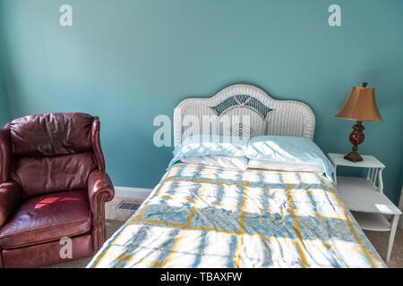 Neue, saubere Bett mit Daunendecke Wicker rattan Kopfteile Tabelle vintage beach blue kissen im Schlafzimmer im Haus Haus mit Leder mahagoni Sessel - Stockfoto