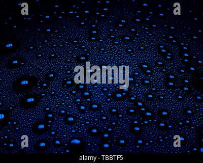 Wassertropfen auf einem blauen Hintergrund. Makro der Kondensation in Kunststoffflasche. Tröpfchen in low light Close-up. - Stockfoto