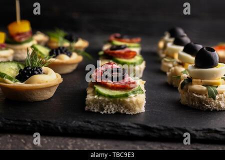 Schiefer Teller mit leckeren Häppchen auf dunklen Tisch, Nahaufnahme - Stockfoto