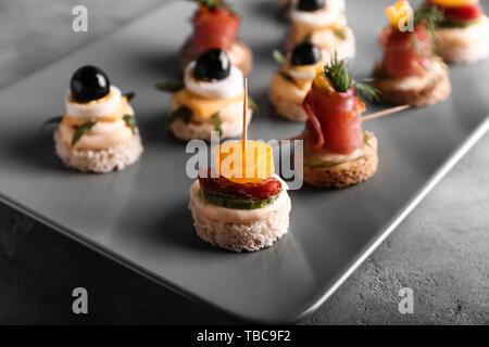 Mit leckeren Häppchen auf grauen Tischplatte, Nahaufnahme - Stockfoto