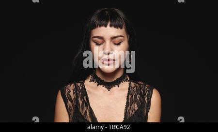 Frau mit Mode piercing auf Lippen auf schwarzem Hintergrund isoliert. Portrait einer jungen gotischen Frau mit geschlossenen Augen. - Stockfoto