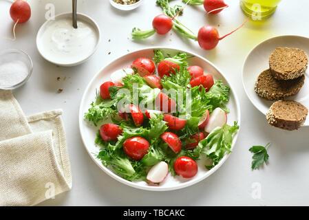 Gesunde Gemüse Salat aus Rettich und Salatblätter auf dem Teller über weiß Tisch aus Stein. Vitamin Frühjahr Salat aus frischem Gemüse. - Stockfoto