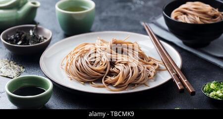 Soba Nudeln mit Sauce und grünem Tee. Japanisches Essen. Schwarzer Schiefer Hintergrund. - Stockfoto