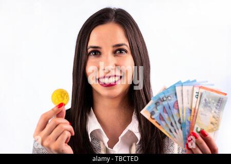 Virtuelle cryptocurrency Geld Bitcoin goldene Münzen und Banknoten in den Händen einer Frau mit roten Nagellack. Schöne weibliche Modell lächelnd. Die - Stockfoto