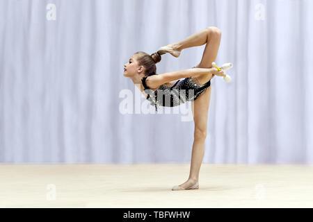 Kleine Turnerin mit unterschiedlichen schwer bewegt sich mit einer Vereine auf der Bühne, die an die rhythmische Gymnastik Wettbewerb, schöner Sport für Mädchen - Stockfoto