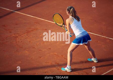 Luftaufnahme eines weiblichen tennis player auf einem Hof bei übereinstimmen. Junge Frau Tennis spielen. Hoher Blickwinkel betrachten. Stockfoto