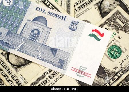 Eine Nahaufnahme Bild eines 5 somoni Bank Note aus Tadschikistan in Makro mit einem Hintergrund von amerikanischen Dollarnoten - Stockfoto