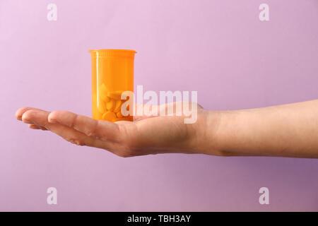 Weibliche hand mit Pillen in Glas auf farbigen Hintergrund - Stockfoto