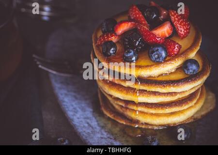 Pfannkuchen mit frischen Beeren und Ahornsirup auf dunklem Hintergrund. Klassische amerikanische hausgemachtes Frühstück. - Stockfoto