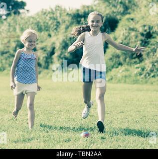 Zwei kleine glückliche Mädchen spielen mit Ball im Freien, zusammen laufen im Sommer Park - Stockfoto