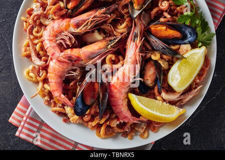 Traditionelle spanische Fideua, eine Nudel Paella mit Meeresfrüchten - Riesengarnelen, weißen Fisch Fleisch, Tintenfische, Muscheln auf einem weißen Teller auf einen konkreten Tisch serviert - Stockfoto
