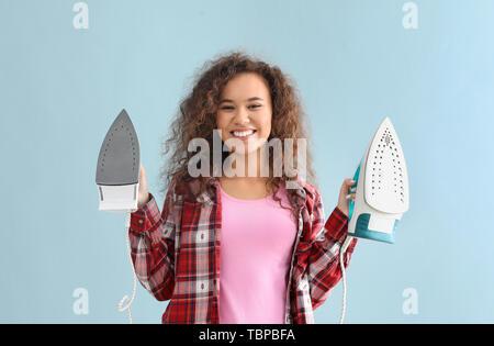Junge Frau mit Eisen auf grauem Hintergrund - Stockfoto