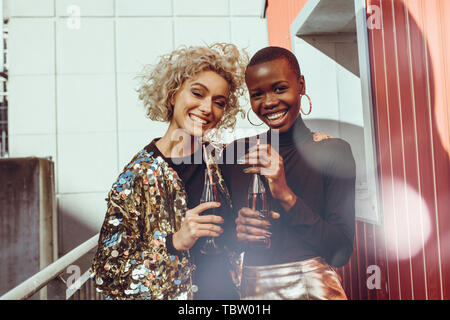 Multi-ethnischen Frauen gemeinsam im Freien mit Cola. Zwei junge weibliche Freunde sozialisieren und Drinks auf der Terrasse im Freien. - Stockfoto