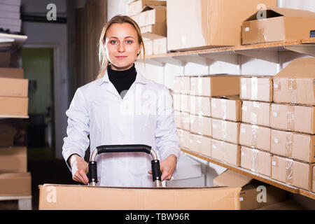 Porträt der jungen Arbeiterin Transport Warenkorb Karton Fälle in Storage