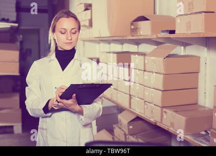 Portrait der weiblichen Arbeitnehmer Transport Warenkorb Karton Fälle in Storage