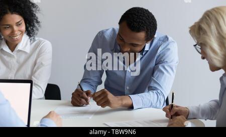 Afrikanische amerikanische Geschäftsmann und reife Geschäftsfrau unterzeichnen Vertrag - Stockfoto