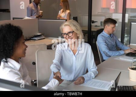 Reife Geschäftsfrau zitternden Hand der afrikanischen amerikanischen Mitarbeiter - Stockfoto