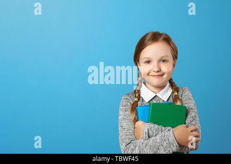 Closeup Portrait von einem kleinen Mädchen Schülerin auf einem blauen Hintergrund. Das Kind hält Bücher. Der Begriff der Bildung und Schule. Platz kopieren - Stockfoto