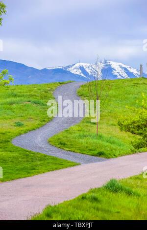 Gepflasterte Wege, auf einem Hügel mit leuchtenden grünen Gräsern bedeckt - Stockfoto