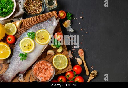 Frischer Fisch Wolfsbarsch und Zutaten zum Kochen. Roher Fisch Wolfsbarsch mit Gewürzen und Kräutern auf schwarzem Schiefer Tisch. Meeresfrüchte Konzept und Ansicht von Oben - Stockfoto