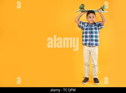 Portrait von niedlichen kleinen Jungen mit Skateboard auf farbigen Hintergrund - Stockfoto
