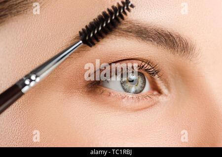 7/8-Ansicht von Frau mit Augenbrauen Pinsel in der Nähe der Augenbrauen - Stockfoto