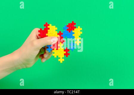 Kind hand mit bunten Herzen auf grünem Hintergrund. Welt Autismus Bewußtsein Tag Konzept - Stockfoto