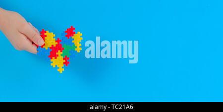 Kind hand mit bunten Herzen auf blauem Hintergrund. Welt Autismus Bewußtsein Tag Konzept - Stockfoto