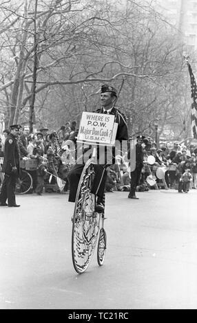"""Ein Mann mit einem Schild mit der Aufschrift 'Wo ist POW große Don Cook USMC?"""" reitet ein penny-farthing oder hohe Rad Fahrrad, im Vietnam Krieg beteiligten - in Verbindung stehende Haus mit Ehre Parade, New York City, New York, 31. März 1973. () - Stockfoto"""