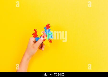 Kind hand mit bunten Herzen auf gelben Hintergrund. Welt Autismus Bewußtsein Tag Konzept - Stockfoto