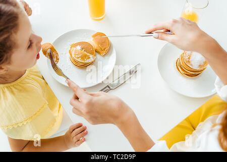 Ansicht von oben von Mutter Fütterung Tochter mit Pfannkuchen - Stockfoto