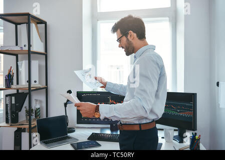 Gute Nachrichten Glückliche junge Geschäftsmann oder Händler in Brillen und formale Abnutzung an den Charts suchen und lächelnd, während vor Computerbildschirmen in modernen Büro. Börsenmakler. Forex Markt. Handel Konzept