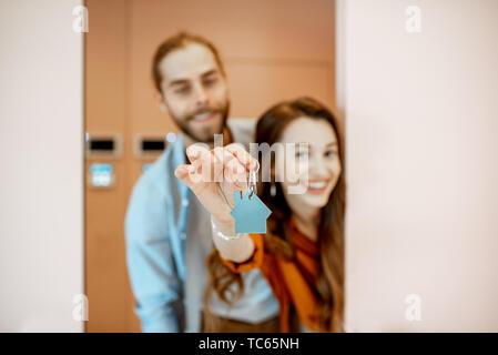 Porträt eines jungen Paares, die Tür mit dem Schlüssel an der Korridor der Neue, moderne Wohnung. Konzept der glückliche Immobilieneigentümer - Stockfoto